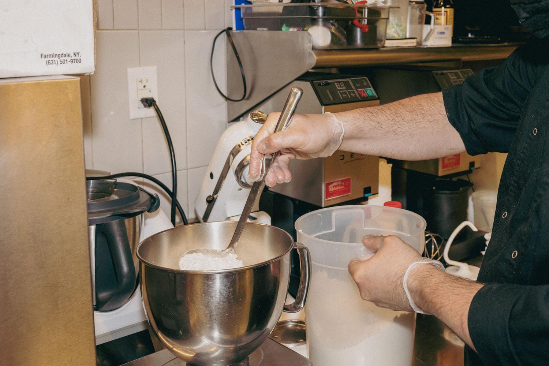 A person pouring flour into a bowl.