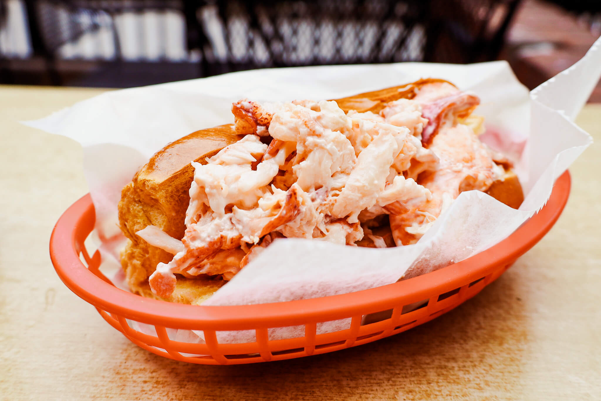 A lobster roll in a red basket.