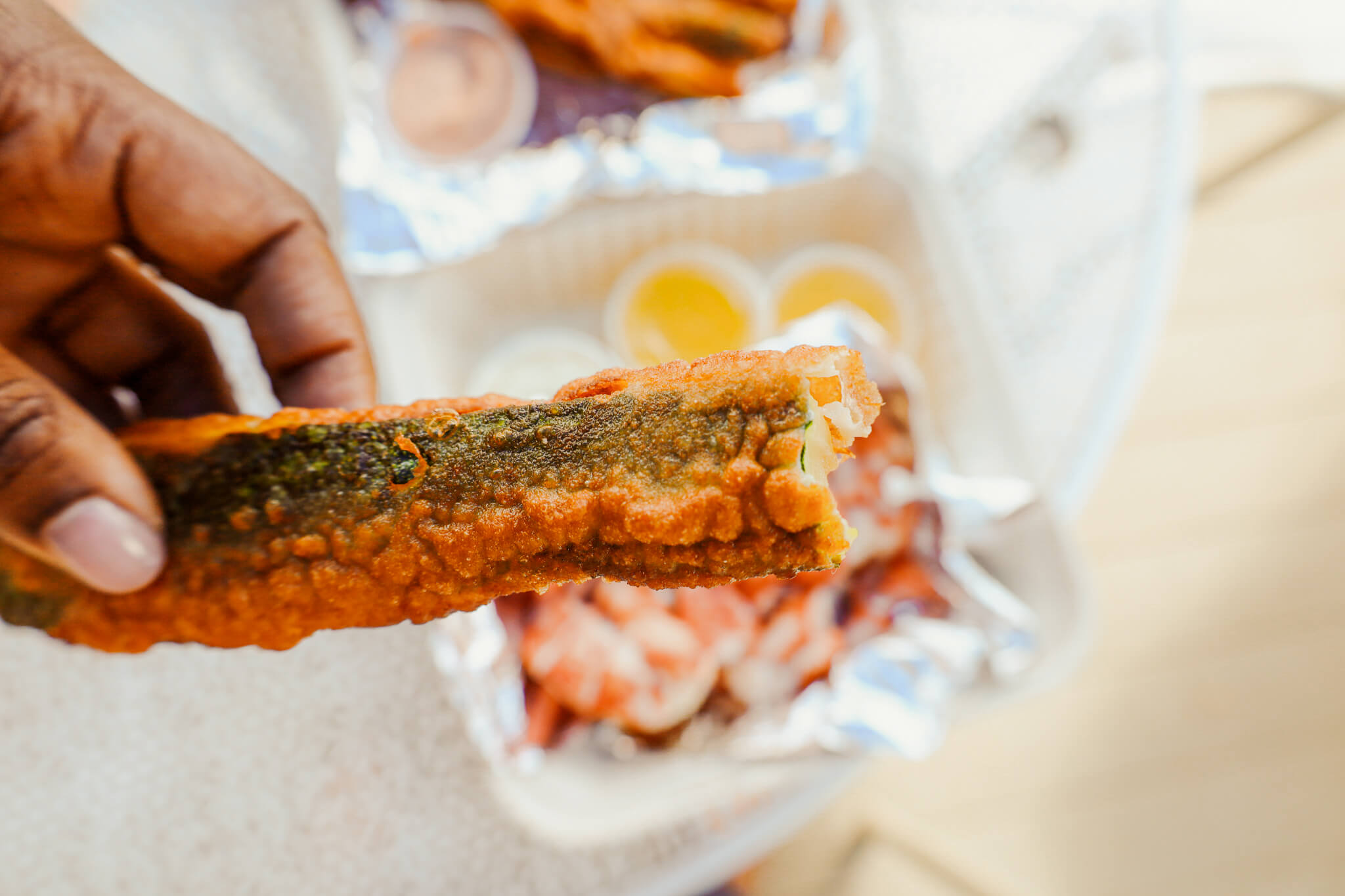 A person holding a fried zucchini.