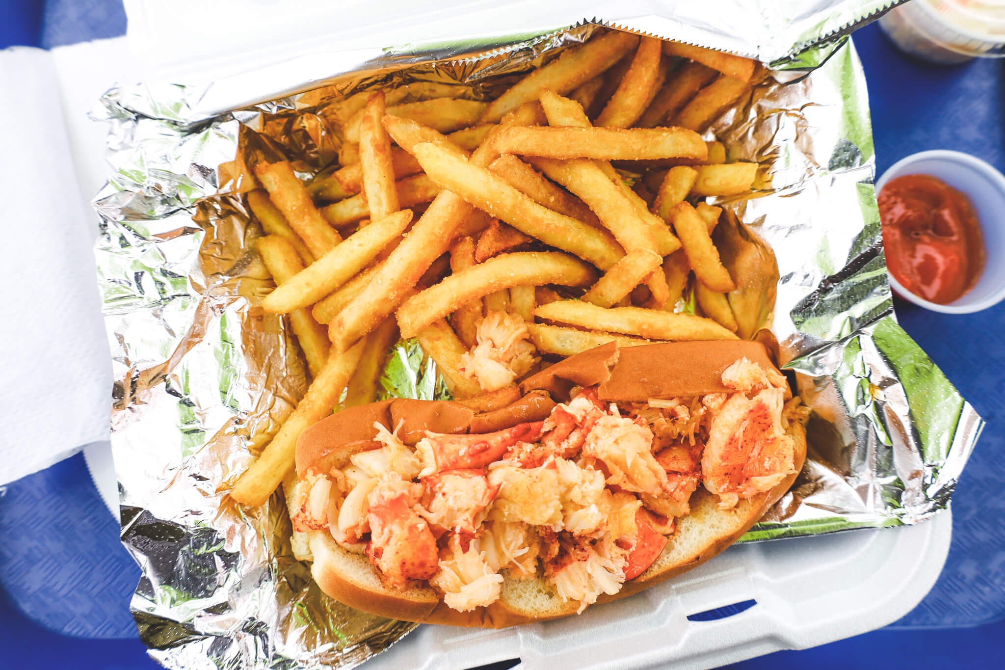 A lobster roll served with crispy french fries.