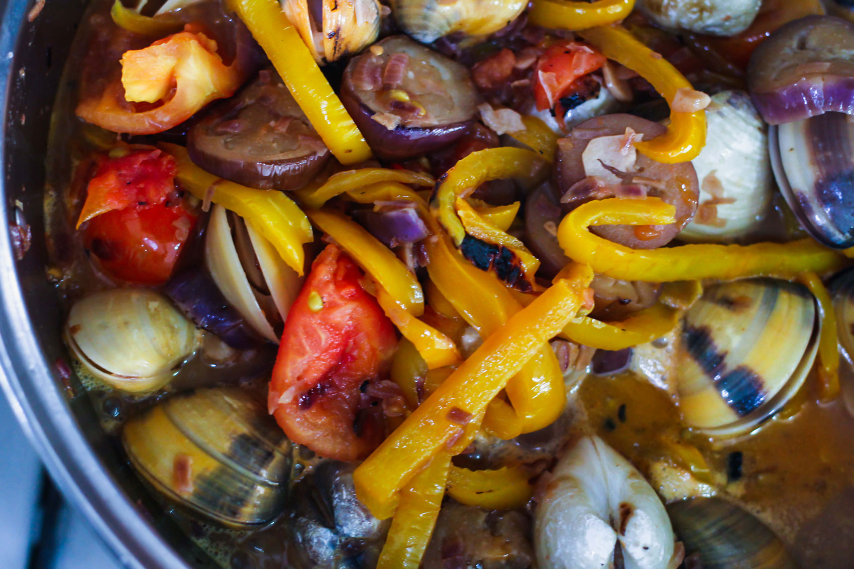 Clams, sliced peppers, eggplant and other ingredients boiling in a pot.