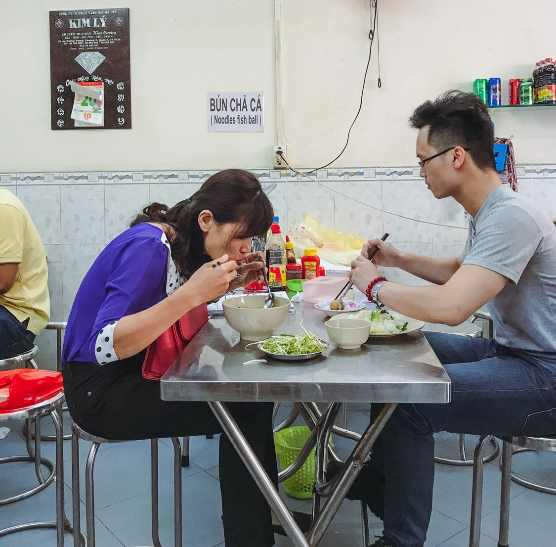 Two people enjoying their food at a small table.
