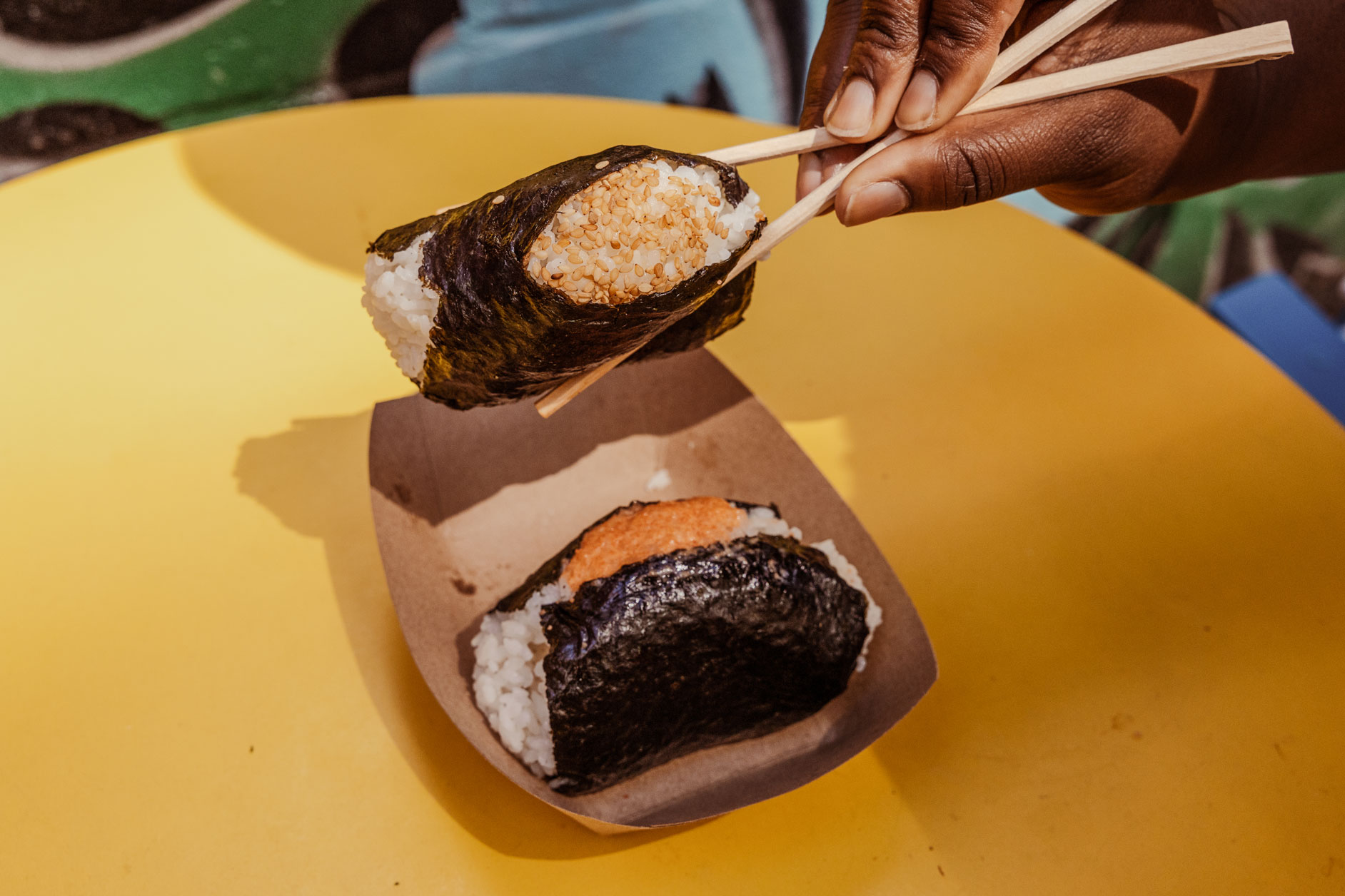 A person holding a rice ball in between two chopsticks.