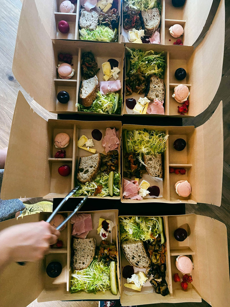 A person putting together picnic boxes.