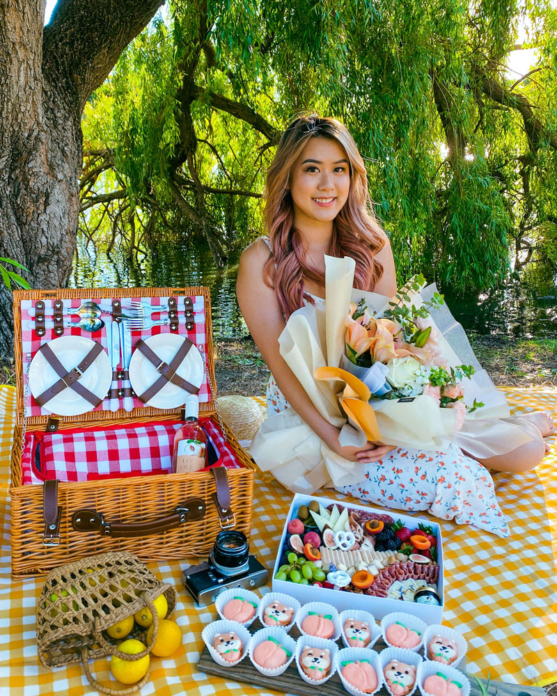 A person posing for a photo sitting at a picnic.