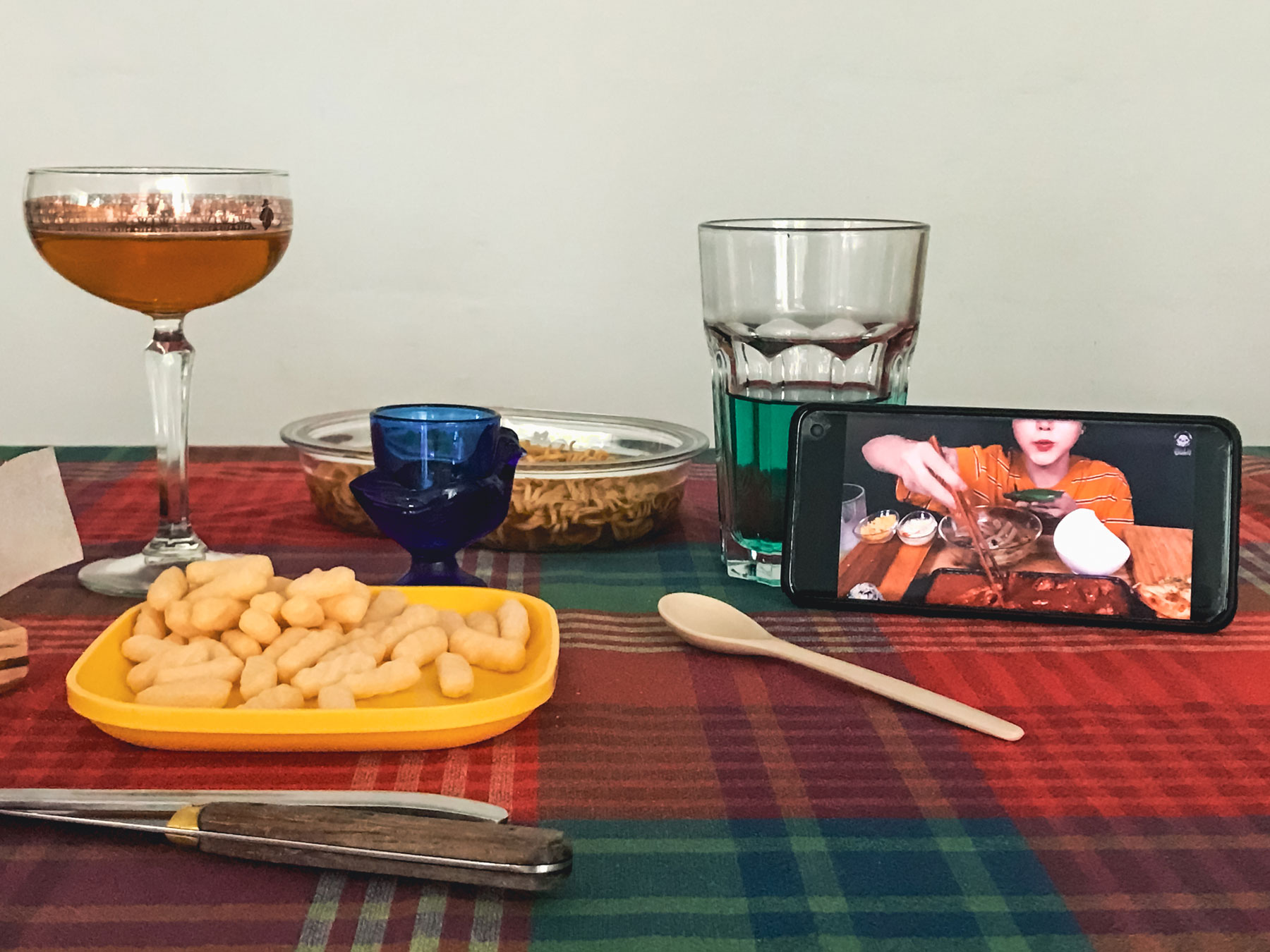 A table set for one with an open smart phone on the table.