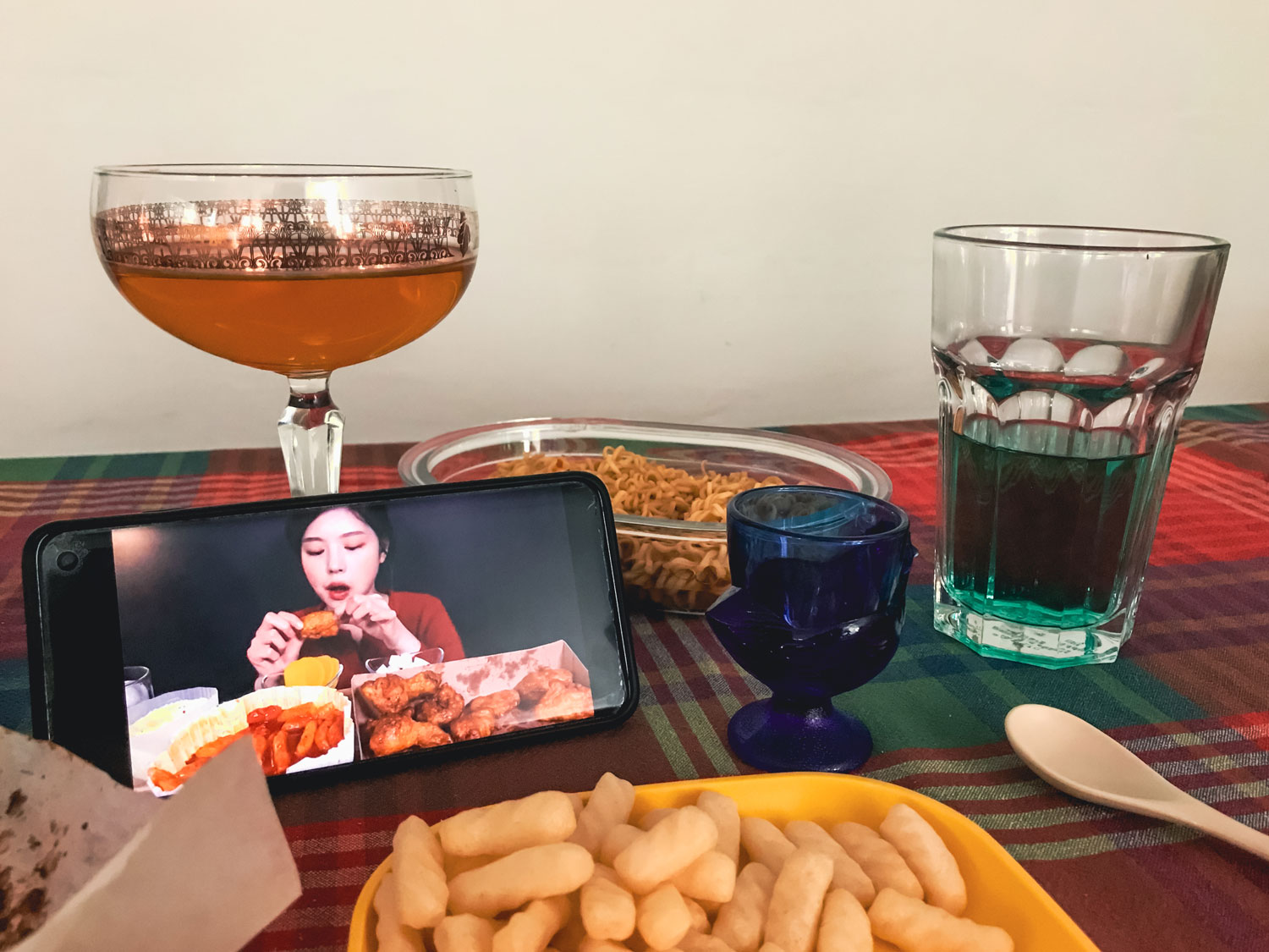 Food for one and a smart phone displaying a person eating.