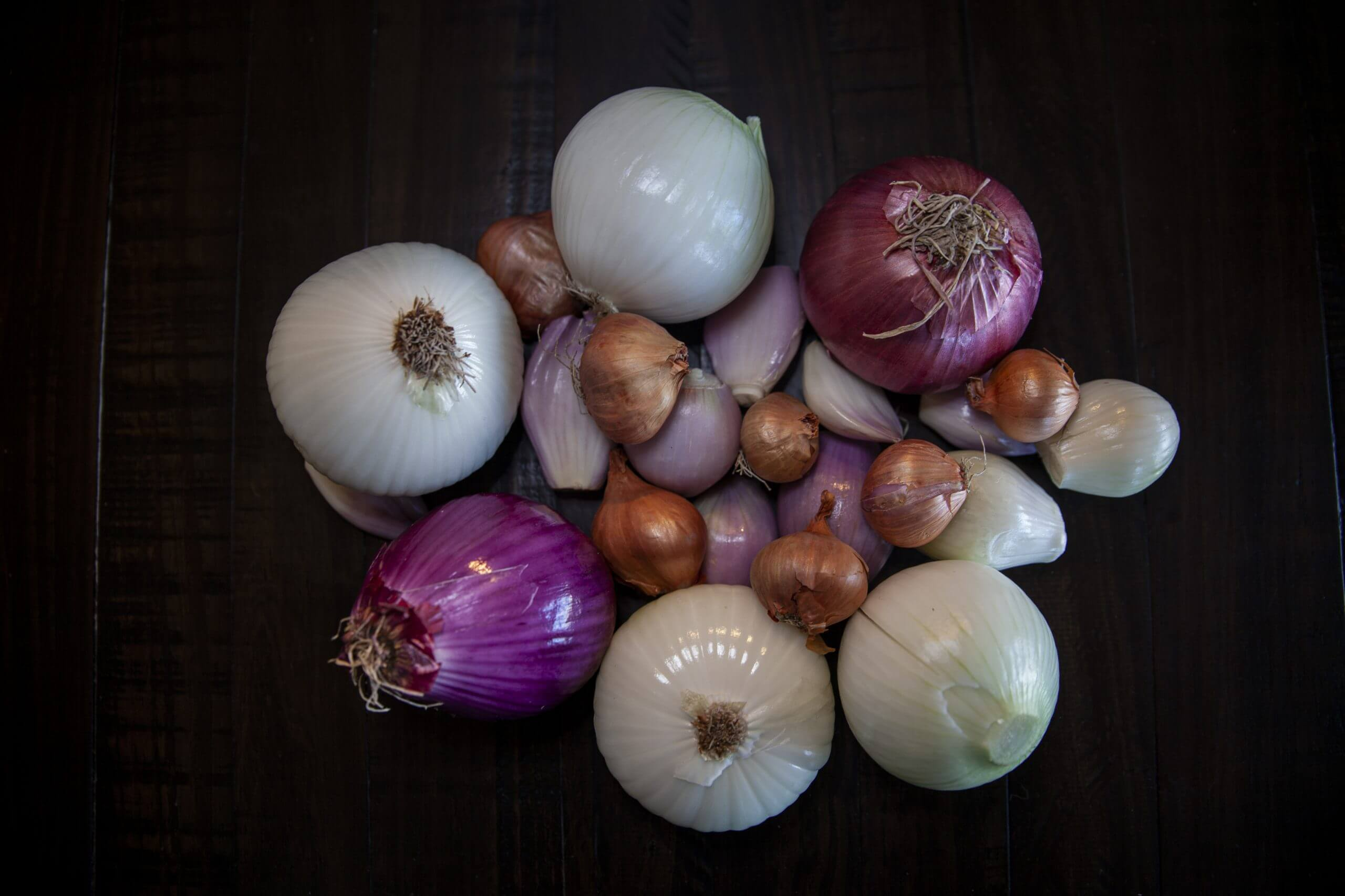 Assorted onions and shallots resting on a dark table.