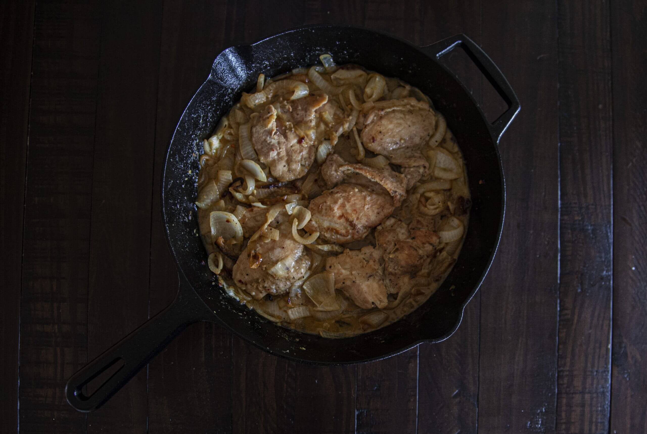 A cast iron skillet holding chicken thighs and caramelized onions.