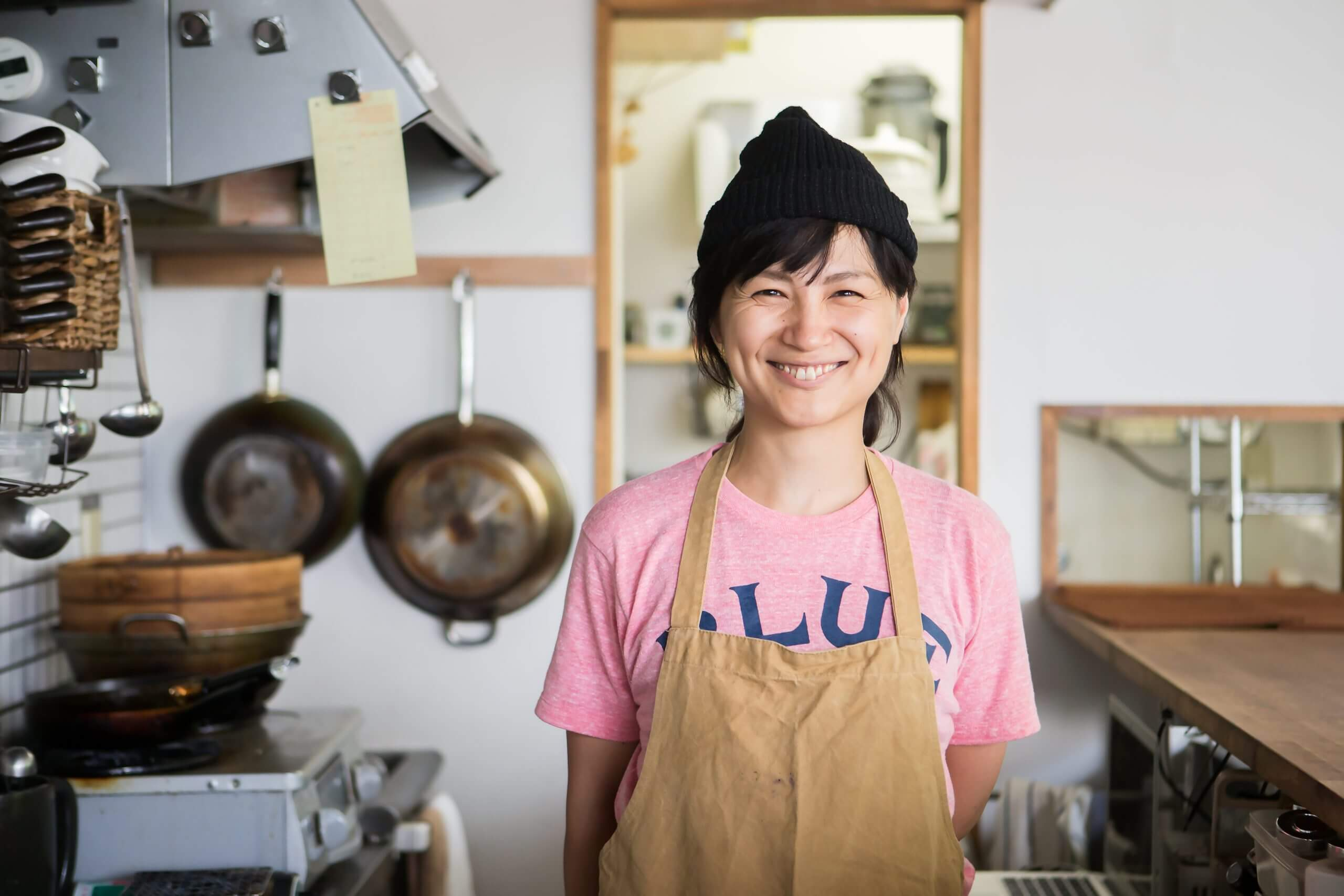 A woman in a canvas apron and pink shirt happily smiling at you from her kitchen.