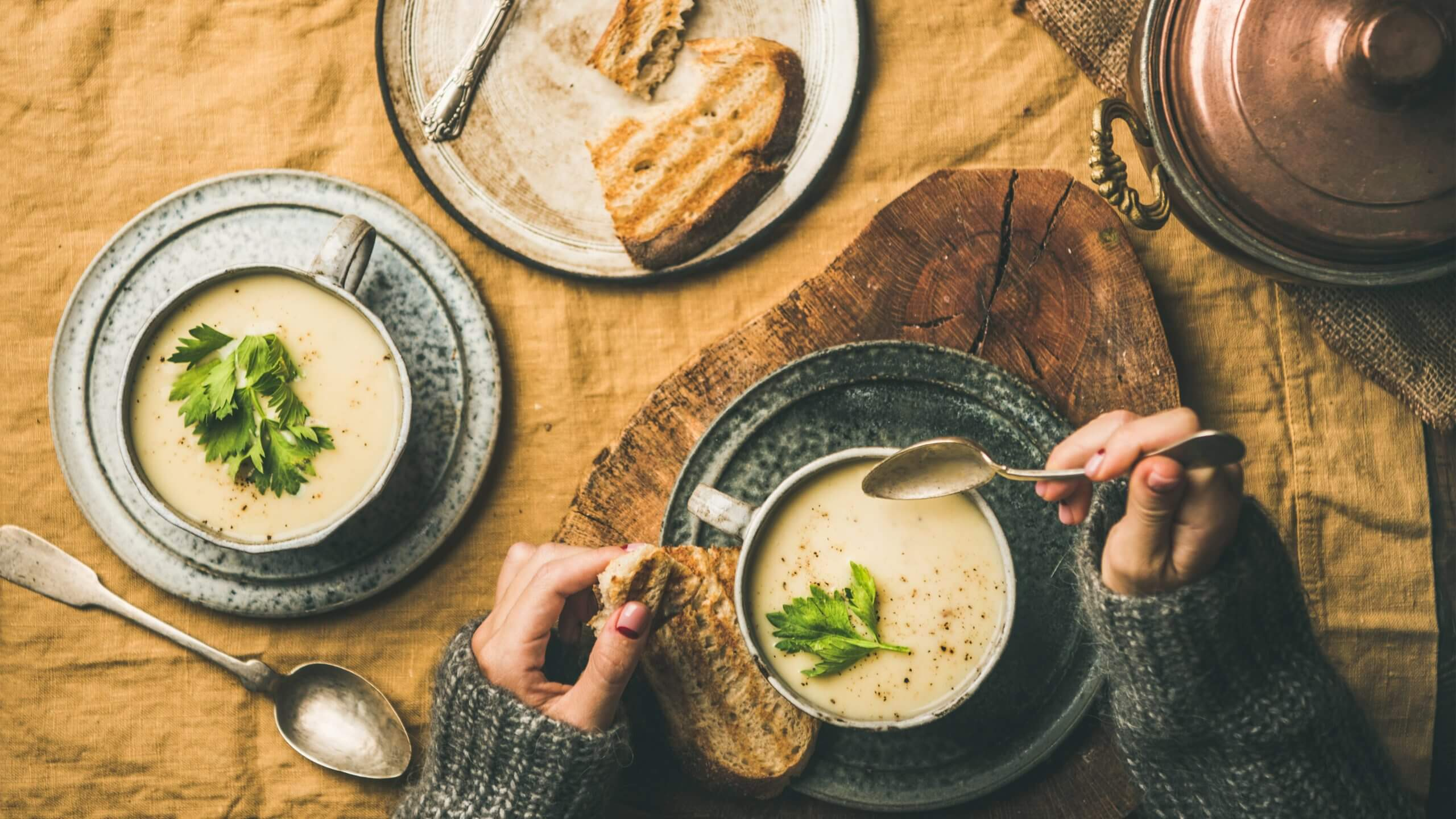 A woman enjoying a bowl of creamy soup with a side of toasted bread.
