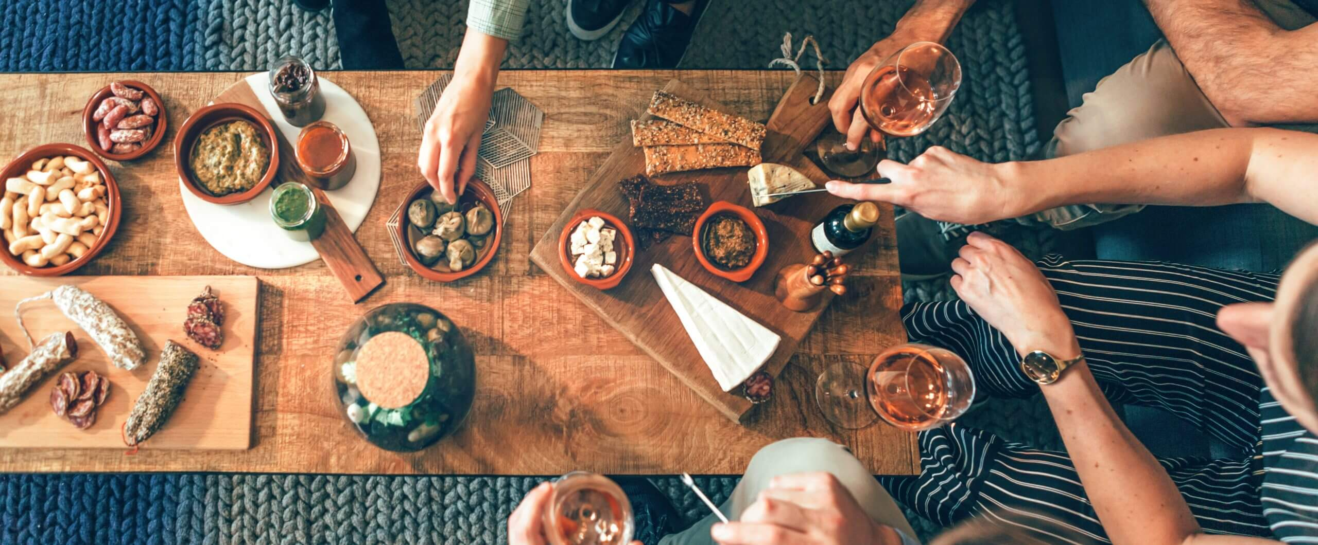 A gathering of friends sitting around a coffee table sharing small eats and sipping wine.
