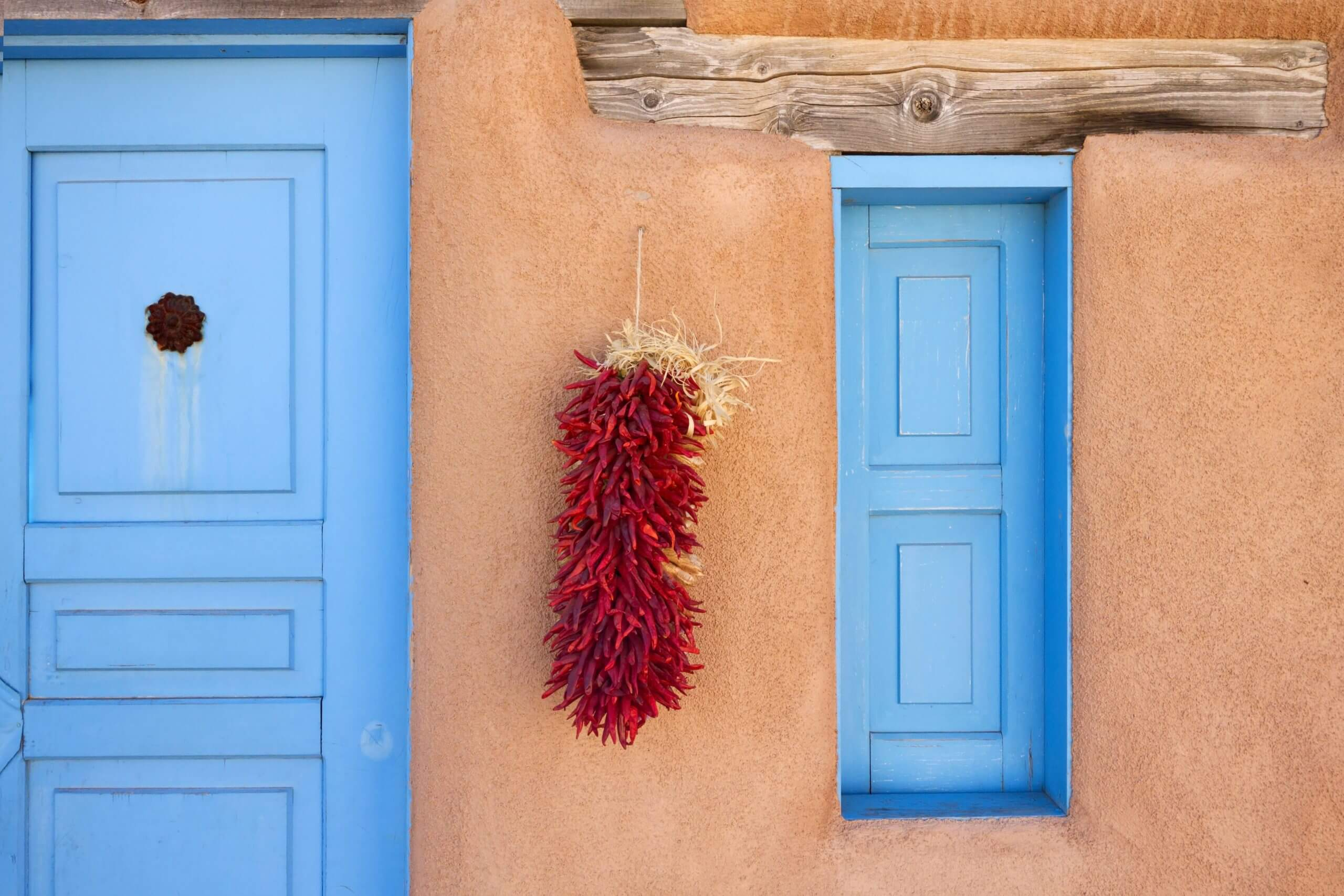 An adobe constructed household adorned with a batch of hanging dried, red chile peppers.