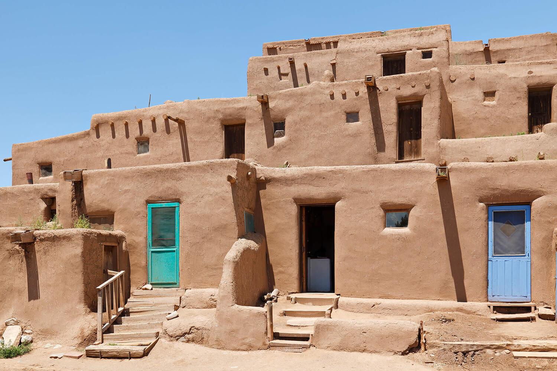 Historic adobe households engulfed bright in sunlight.