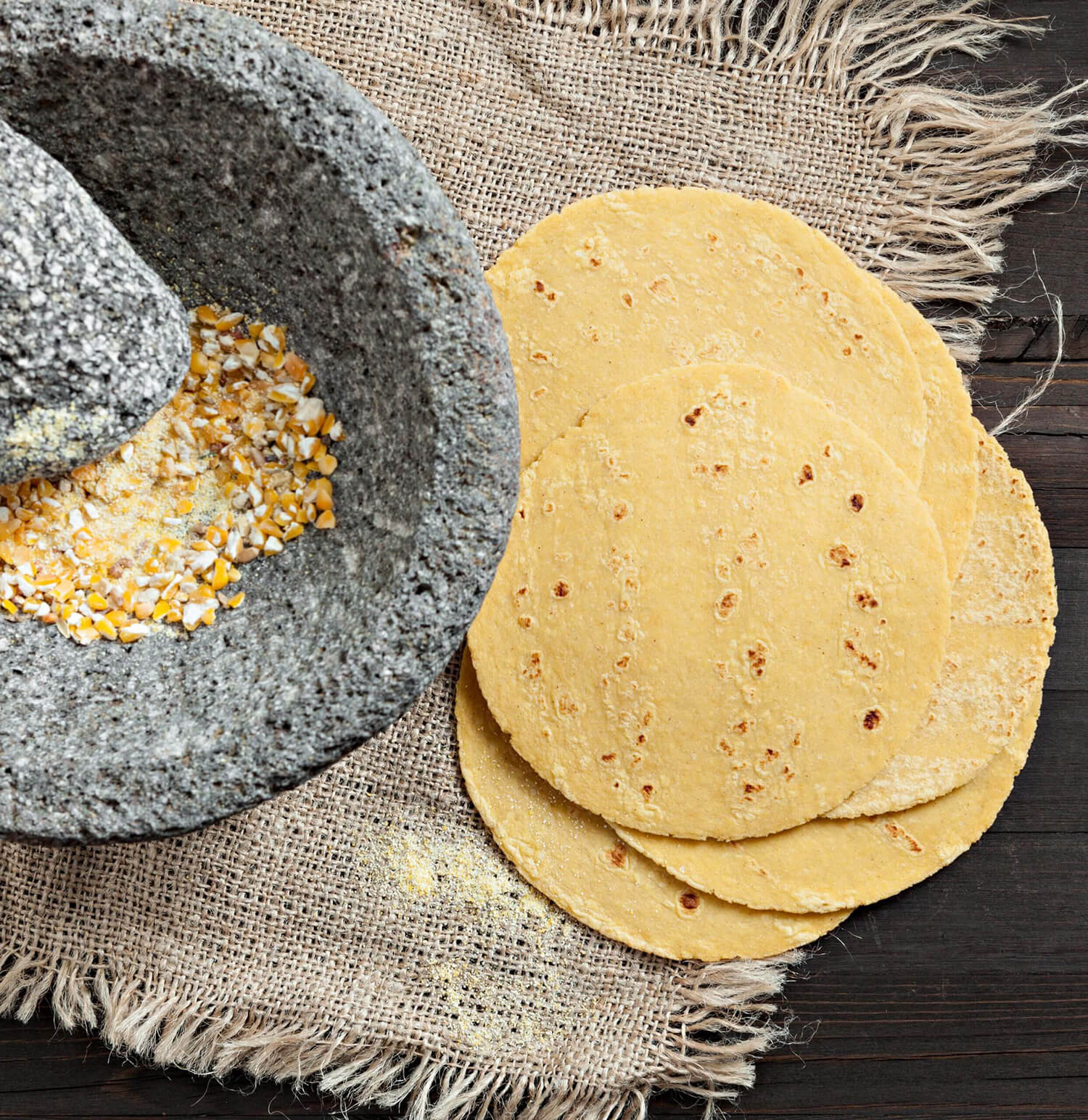 A wooden table with homemade tortillas next to a stone grinder filled with dried corn.