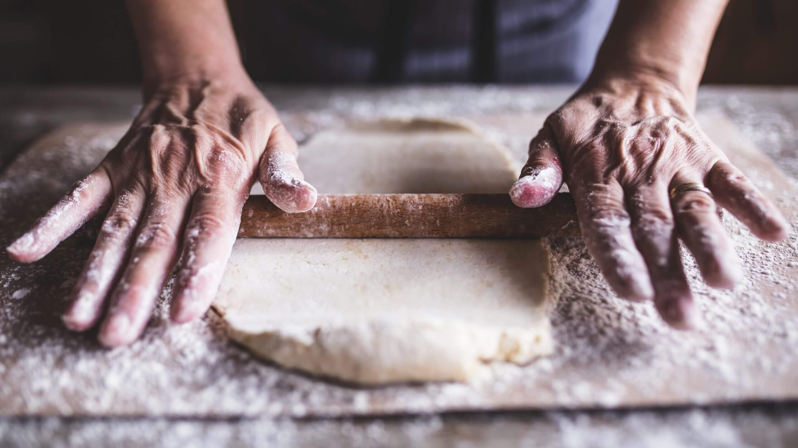 Strong hands masterfully rolling dough covered in flour on a wooden cutting board.
