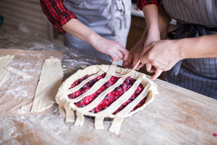 Two people weaving thinly sliced, rolled out dough into an intricate pie crust.