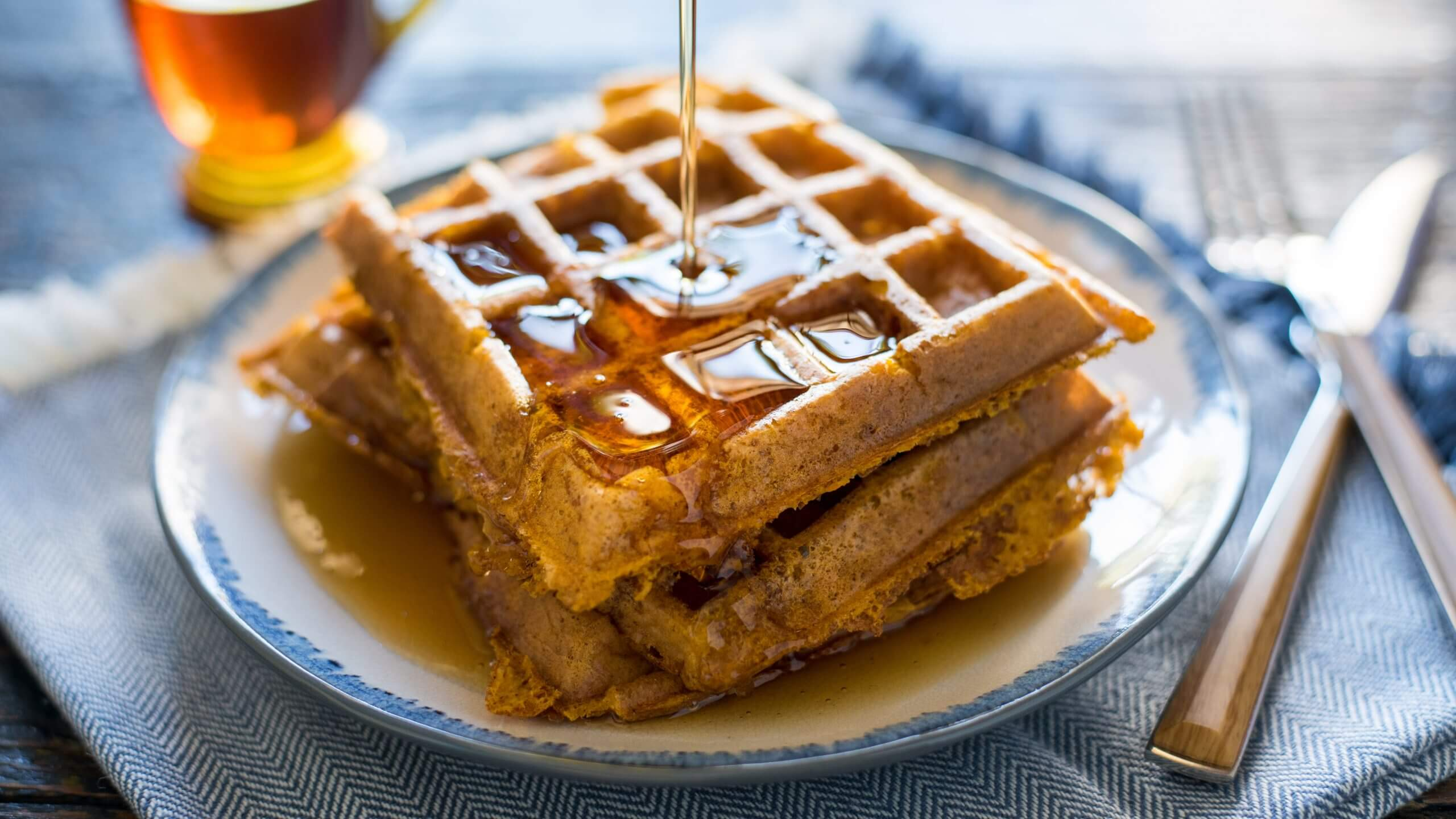 A close-up of freshly made, crispy waffles being doused in in silky syrup.