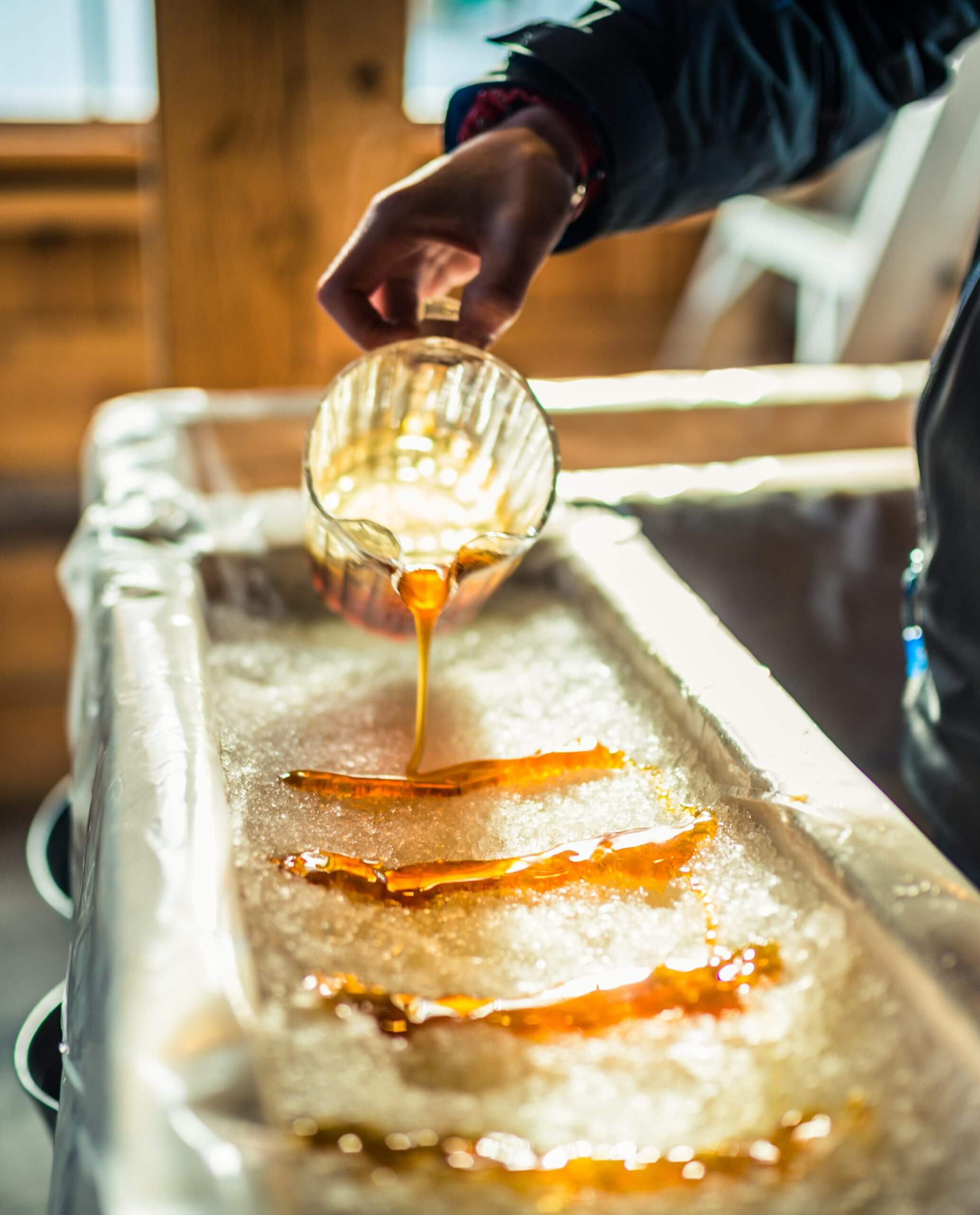 A close-up of a person gently pouring rows of syrup into packed snow for a sweet treat.