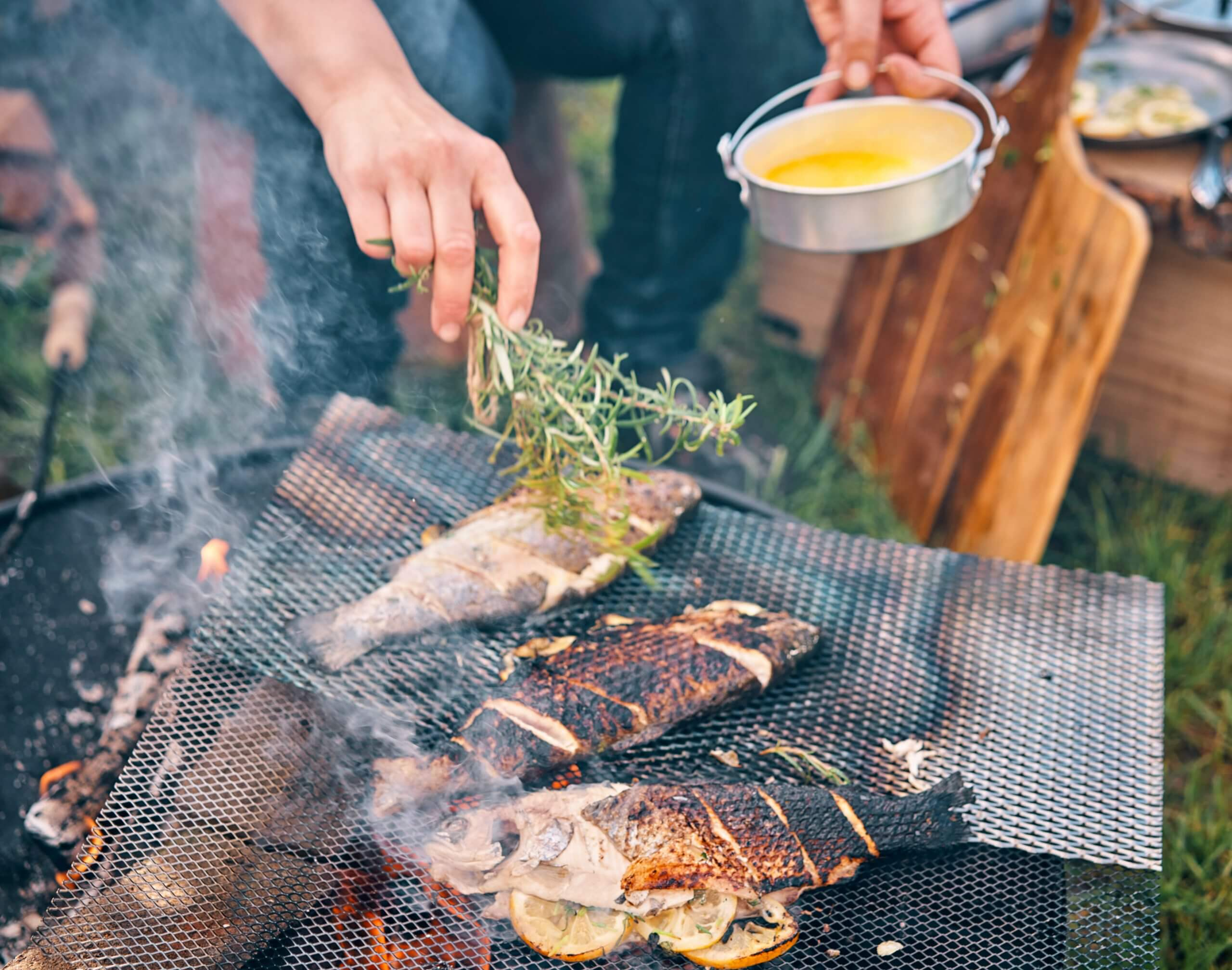 A person grilling three freshly caught fish stuffed with sliced lemons over an open fire pit.