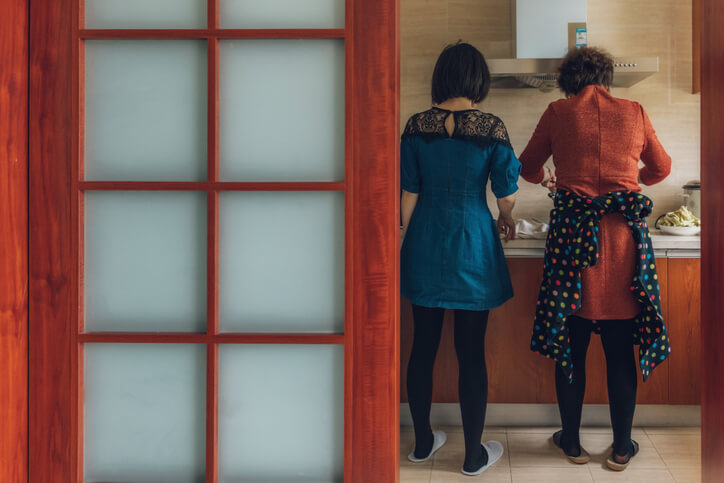 Two women standing side by side as they focus on the cooking task at hand.