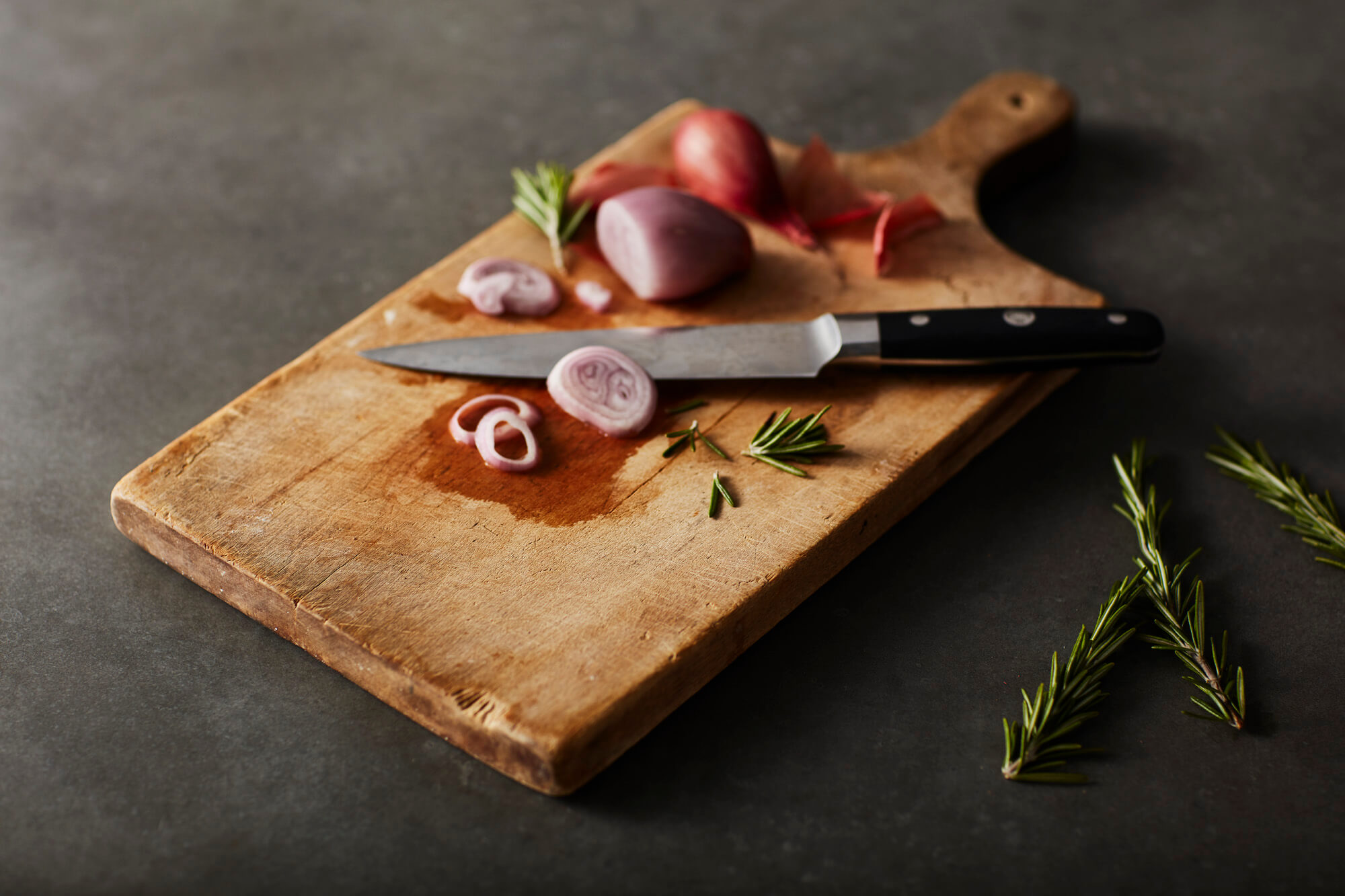 Sliced onions and thyme resting on a wooden cutting board.