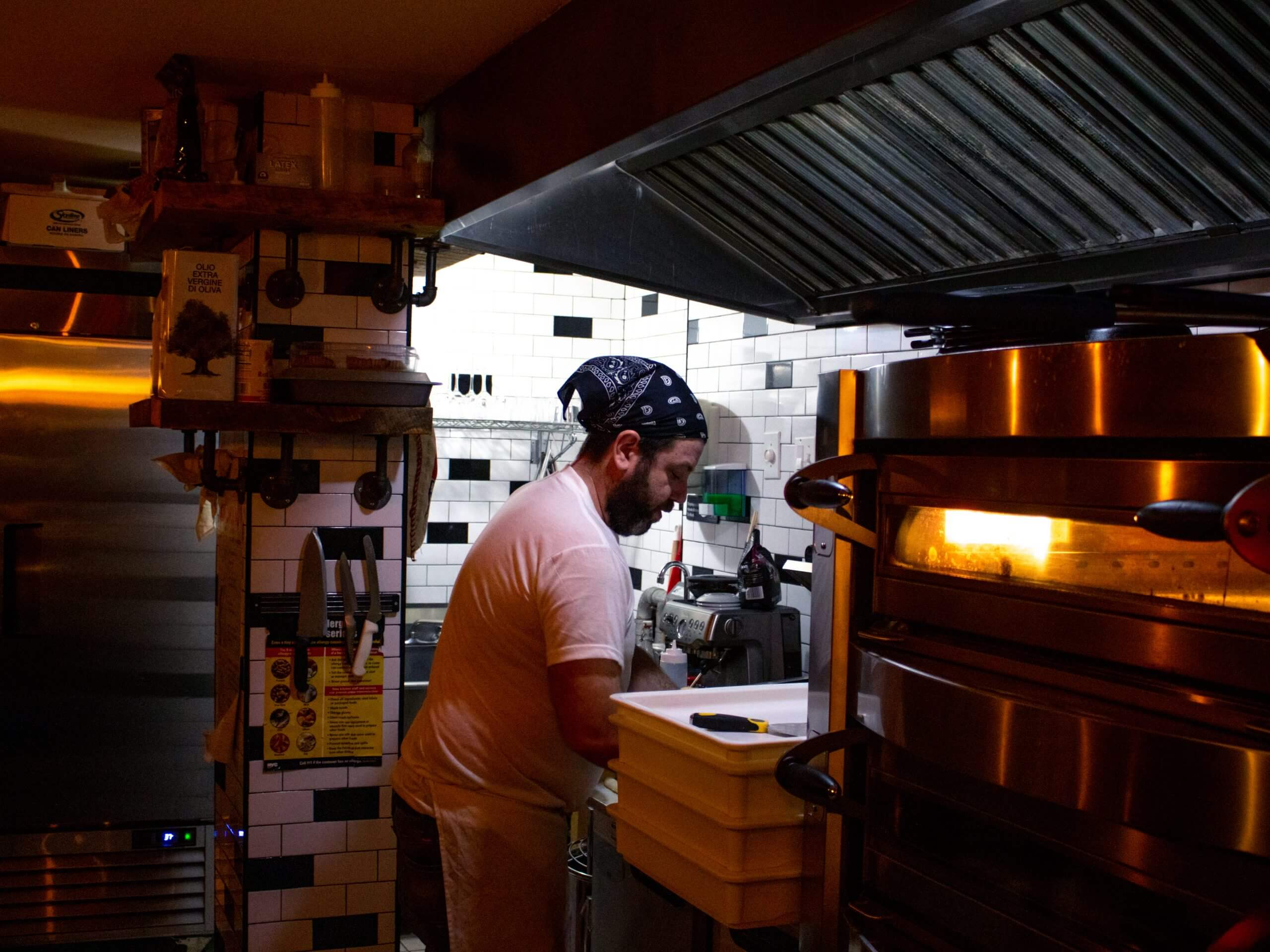 A man standing in his restaurant's kitchen working diligently over a pizza.
