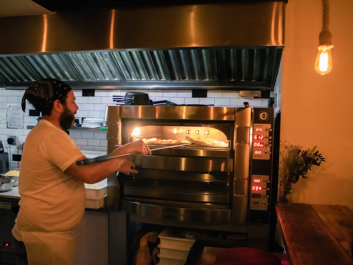 A man expertly working pizzas into a stainless steel pizza oven in a restaurant kitchen.