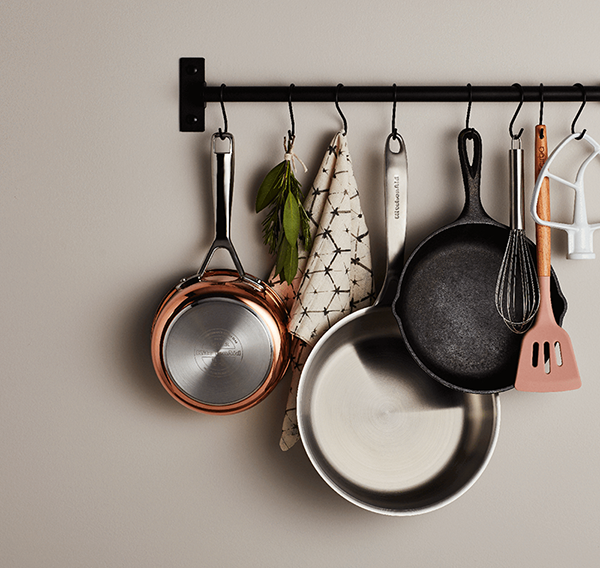 A collection of assorted pans and cookware hanging from a wall-mounted pot rack.
