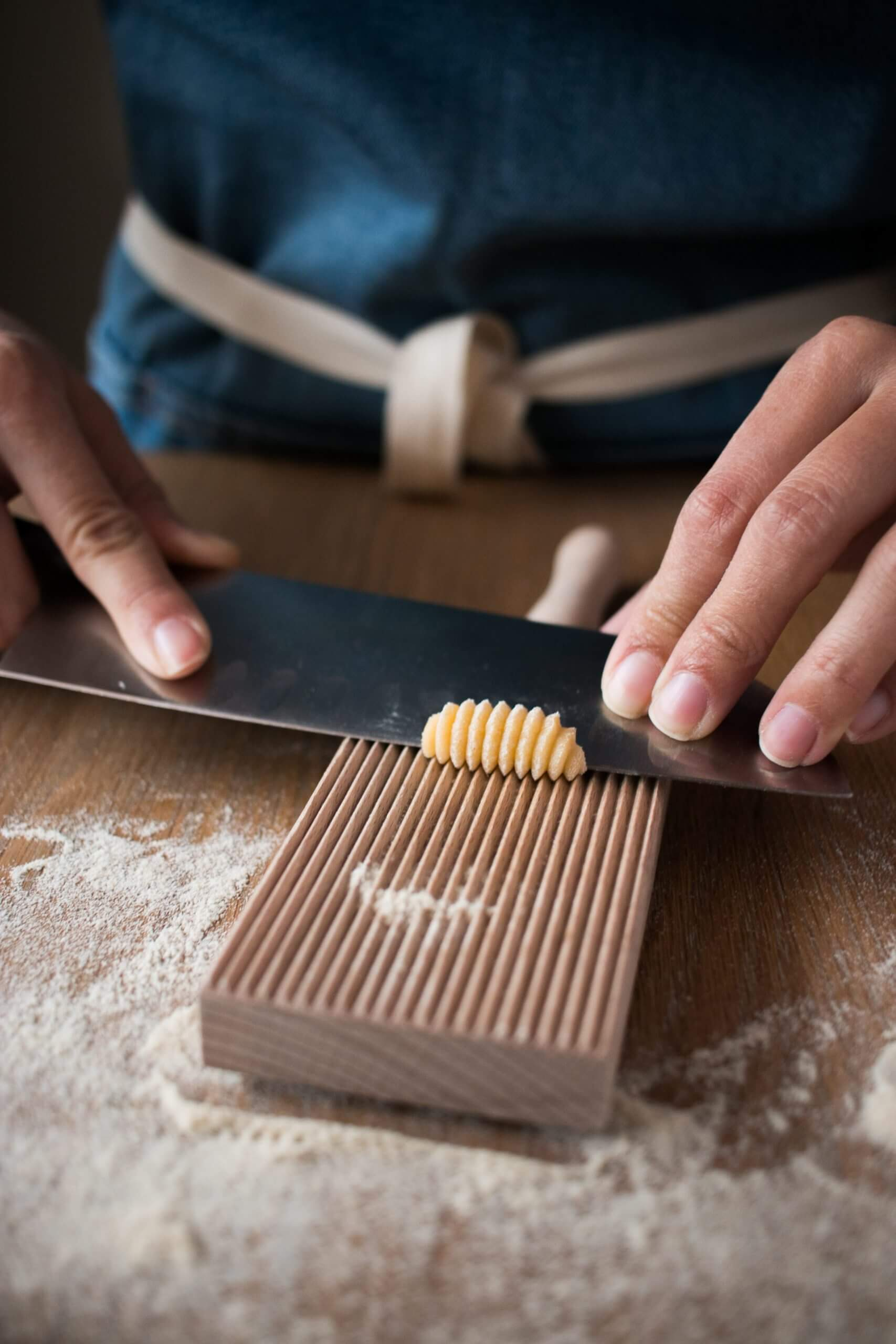 Experienced hands rolling out homemade gnocchi on a gnocchi roller board with a chef's knife.