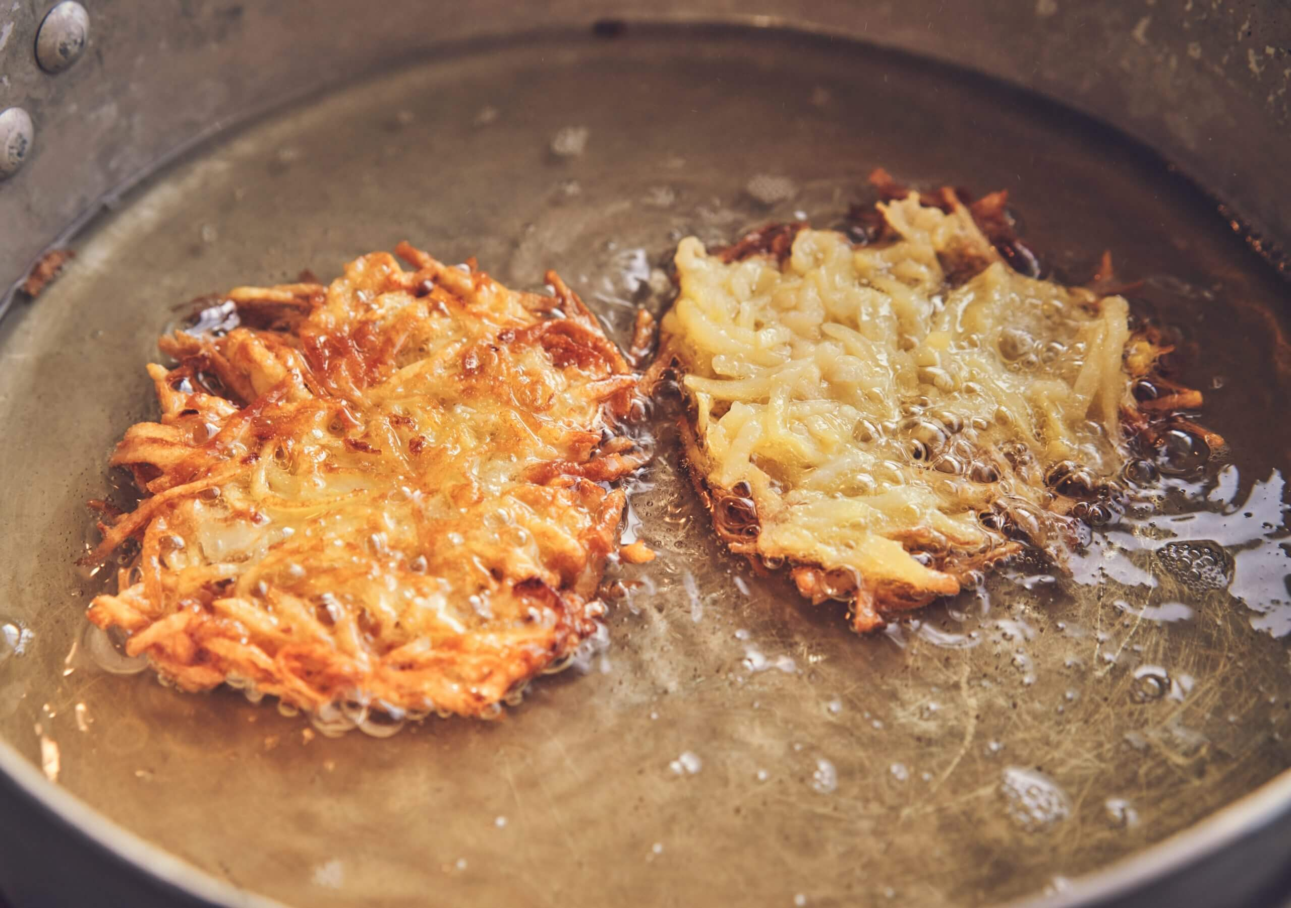Two potato pancakes decadently frying in a pan of glistening oil.